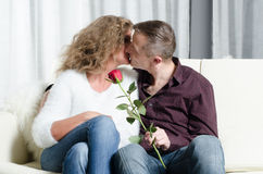 Couple with rose kissing on couch Stock Images
