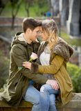 Couple with rose in love kissing on street alley celebrating Valentines day with passion sitting on city park. Candid and romantic portrait of beautiful European Royalty Free Stock Photos