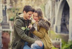 Couple with rose in love kissing on street alley celebrating Valentines day with passion sitting on city park. Candid and romantic portrait of beautiful European Royalty Free Stock Images