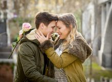 Couple with rose in love kissing on street alley celebrating Valentines day with passion sitting on city park. Candid and romantic portrait of beautiful European Stock Images
