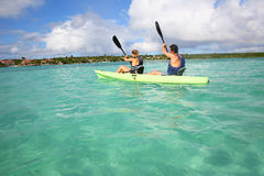 Couple rowing in canoe in a crystal clear water in tropics. Couple canoeing in transparent caribbean sea Stock Image