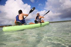 Couple rowing in a canoe in tropics Royalty Free Stock Images