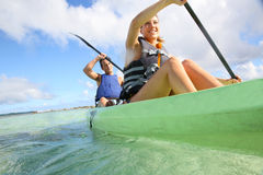 Couple rowing in canoe in tropics. Couple canoeing in transparent caribbean sea Royalty Free Stock Image