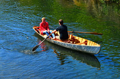Couple Rowing row boat over Avon River Christchurch - New Zealan Stock Photo