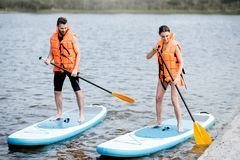 Couple rowing on the stand up paddleboard. Couple in life vests learning to row on the stand up paddleboard on the lake stock photo