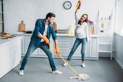 Couple in rubber gloves having fun with mop during. Cleaning kitchen royalty free stock photography