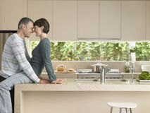Couple Rubbing Noses In Kitchen Royalty Free Stock Images