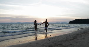 Couple Run From Sea Water Holding Hands Happy Man And Woman On Beach At Sunset During Honeymoon Vacation. Slow Motion 60 stock video footage