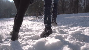 Couple Runing in Snow Park. Young happy boy and girl runing on snow in winter park, 120FPS stock video footage