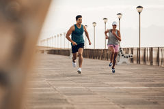 Couple of runners competing on promenade. Couple of runners sprinting along the road by the sea. Fitness couple running on the sea side promenade stock photography