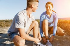 Couple of runners lace their shoes and prepare to jogging Royalty Free Stock Photos