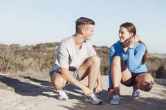 Couple of runners lace their shoes and prepare to jogging Stock Images