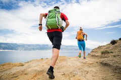 Couple runners running with backpacks on rocku trail at seaside. Couple runners running with backpacks on rocky trail at seaside and mountains. Young women and stock photography