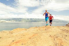 Couple runners running with backpacks on rocku trail at seaside Royalty Free Stock Photography