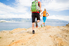 Couple runners running with backpacks on rocku trail at seaside Stock Photos