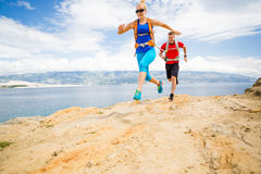 Couple runners running with backpacks on rocku trail at seaside Royalty Free Stock Image