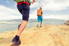 Couple runners running with backpacks on rocku trail at seaside Stock Image