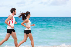 Couple runners running training cardio on beach. Fitness interracial couple runners running on beach. Running couple jogging together outside on ocean background Stock Image