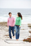 Couple running along beach path holding hands. Smiling Stock Photo