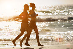 Couple running along the beach at sunset Royalty Free Stock Photo