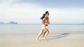 Couple Running Along Beach Talking, Happy Couple Smiling Tourists On Sea Vacation. Slow Motion 120 stock video footage
