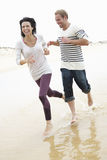 Couple Running Along Beach Together Royalty Free Stock Photos