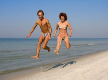 Couple running along sea coast Royalty Free Stock Image