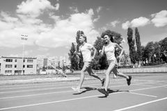 Couple running on arena track. Coach and trainer at workout. Runner on competition and future success. Man and woman sunny outdoor on blue sky. Sport and stock photo