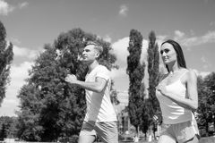 Couple running on arena track. Coach and trainer at workout. Runner on competition and future success. Man and women sunny outdoor on blue sky. Sport and royalty free stock photos