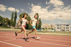 Couple running on arena track. Coach and trainer at workout. Runner on competition and future success. Man and women sunny outdoor on blue sky. Sport and stock photography