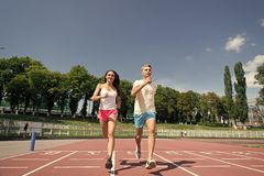 Couple running on arena track. Sport and healthy fitness. Man and women sunny outdoor on blue sky. Coach and trainer at workout. Runner on competition and royalty free stock image