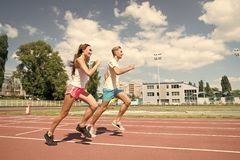 Couple running on arena track. Sport and healthy fitness. Man and women sunny outdoor on blue sky. Coach and trainer at workout. Runner on competition and stock photos