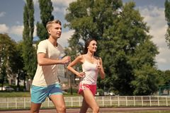 Couple running on arena track. Man and women sunny outdoor on blue sky. Coach and trainer at workout. Runner on competition and future success. Sport and royalty free stock image