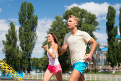 Couple running on arena track. Man and women sunny outdoor on blue sky. Coach and trainer at workout. Runner on competition and future success. Sport and royalty free stock images