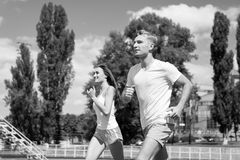 Couple running on arena track. Man and women sunny outdoor on blue sky. Coach and trainer at workout. Runner on competition and future success. Sport and royalty free stock photos