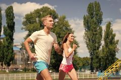 Couple running on arena track. Man and women sunny outdoor on blue sky. Coach and trainer at workout. Runner on competition and future success. Sport and stock photography