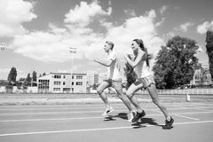 Couple running on arena track. Sport and healthy fitness. Man and women sunny outdoor on blue sky. Coach and trainer at workout. Runner on competition and royalty free stock images