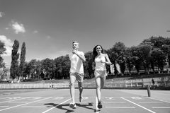 Couple running on arena track. Sport and healthy fitness. Man and women sunny outdoor on blue sky. Coach and trainer at workout. Runner on competition and stock photo