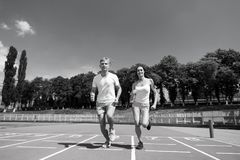 Couple running on arena track. Sport and healthy fitness. Runner on competition and future success. Man and women sunny outdoor on blue sky. Coach and trainer stock image