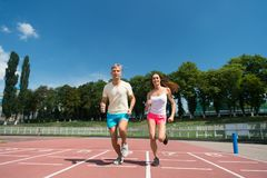 Couple running on arena track. Sport and healthy fitness. Runner on competition and future success. Man and women sunny outdoor on blue sky. Coach and trainer royalty free stock images
