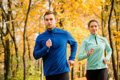 Couple running in autumn nature Royalty Free Stock Photos