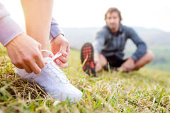 Couple running in autumn nature, stretching, tying shoelaces Royalty Free Stock Photos