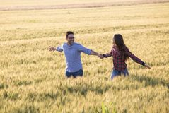 Couple running in barley field stock photography