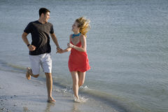 Couple running on the beach. A man and woman holding hands running down the beach Royalty Free Stock Photography