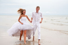 Couple running on a beach. Happy young couple running barefoot on a beach Stock Photos
