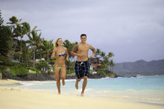 Couple running on the beach. Newly wed couple running on the beach at Lanikai, Hawaii Stock Photos