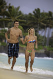 Couple running on the beach. Newly wed couple running on the beach at Lanikai, Hawaii Stock Photography