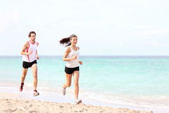 Couple running on beach stock images