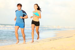 Couple running on beach. Runners jogging during outdoor workout on beautiful beach at sunset. Caucasian man, Asian woman Royalty Free Stock Image