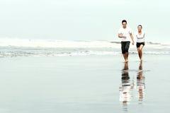 Couple running on the beach Stock Photos